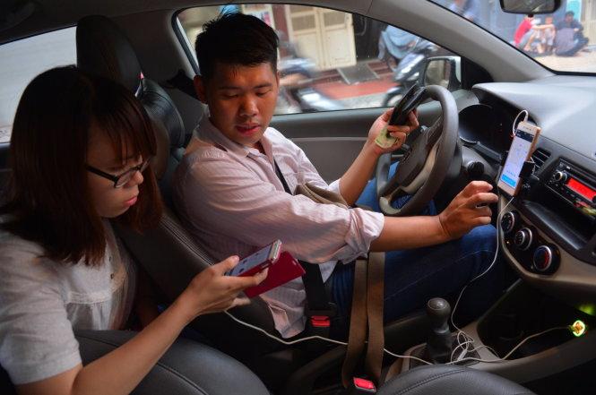 HiÇn nay, lo¡i hình kinh doanh cça Uber ang gây tranh cãi. Các chuyên gia cho rng, kh£ nng bË th¥t thoát thu¿ n¿u quy Ënh tài x¿ Uber chËu trách nhiÇm kh¥u trë thay cho Uber. MÙt khách i xe Uber thanh toán tiÁn m·t cho mÙt chuy¿n i - ¢nh: Quang Ënh