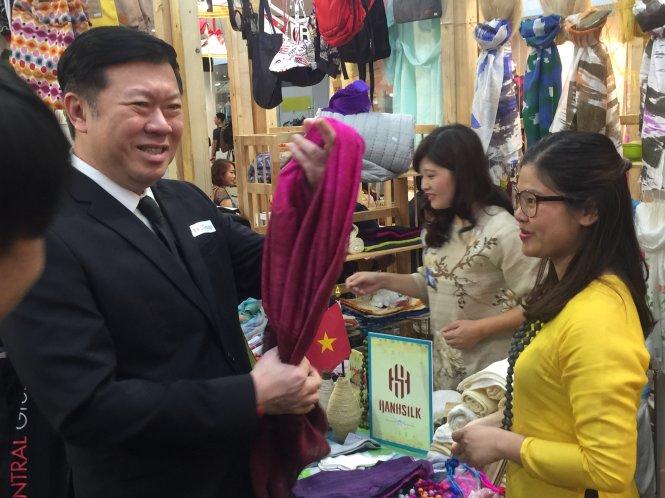 MÙt vË khách Thái Lan tìm hiÃu và sau ó mua 3 chi¿c khn låa VN. ¢nh : Nh° Bình