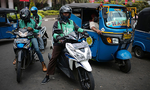 Go-Jek motorcycle drivers and bajaj drivers wait for fares in Jakarta, Indonesia, on Sunday, Aug. 13, 2017. President Joko Widodo is seeking hundreds of billions of dollars to finance an ambitious infrastructure agenda and to boost growth to 7 percent. Photographer: Dimas Ardian/Bloomberg via Getty Images