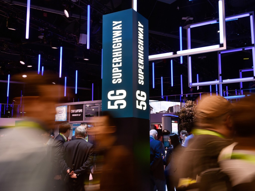 LAS VEGAS, NV - JANUARY 09:  Attendeess pass by signage for 5G technology at the Intel booth during CES 2018 at the Las Vegas Convention Center on January 9, 2018 in Las Vegas, Nevada. CES, the world's largest annual consumer technology trade show, runs through January 12 and features about 3,900 exhibitors showing off their latest products and services to more than 170,000 attendees.  (Photo by David Becker/Getty Images)