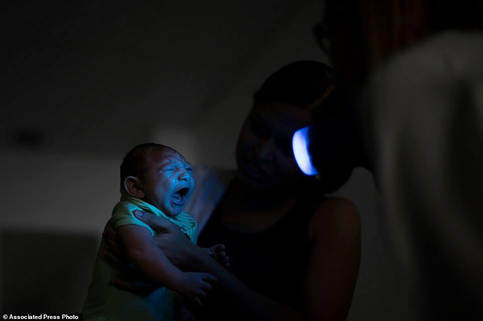 Daniele Ferreira dos Santos ẵm con trai Juan Pedro đi khám bệnh tại tổ chức Altino Ventura ở Recife, bang Pernambuco, một vùng đang có hàng trăm ca bệnh đầu teo được phát hiện.