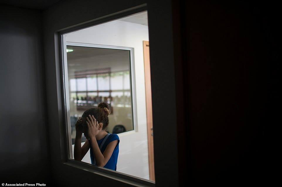 Chị của be Juan Pedro – Jennipher Karine nhìn vào trong căn phòng em Pedro đang được khám bệnh tại Altino Ventura foundation ở Recife. 11. Gleyse Kelly, 27, ẵm đứa con gái Maria Giovanna sinh ra mắc chứng đầu teo bên ngoài ngôi nhà của hai vợ chồng ở Recife.