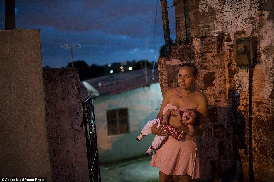 Gleyse Kelly, 27, ẵm đứa con gái Maria Giovanna sinh ra mắc chứng đầu teo bên ngoài ngôi nhà của hai vợ chồng ở Recife.