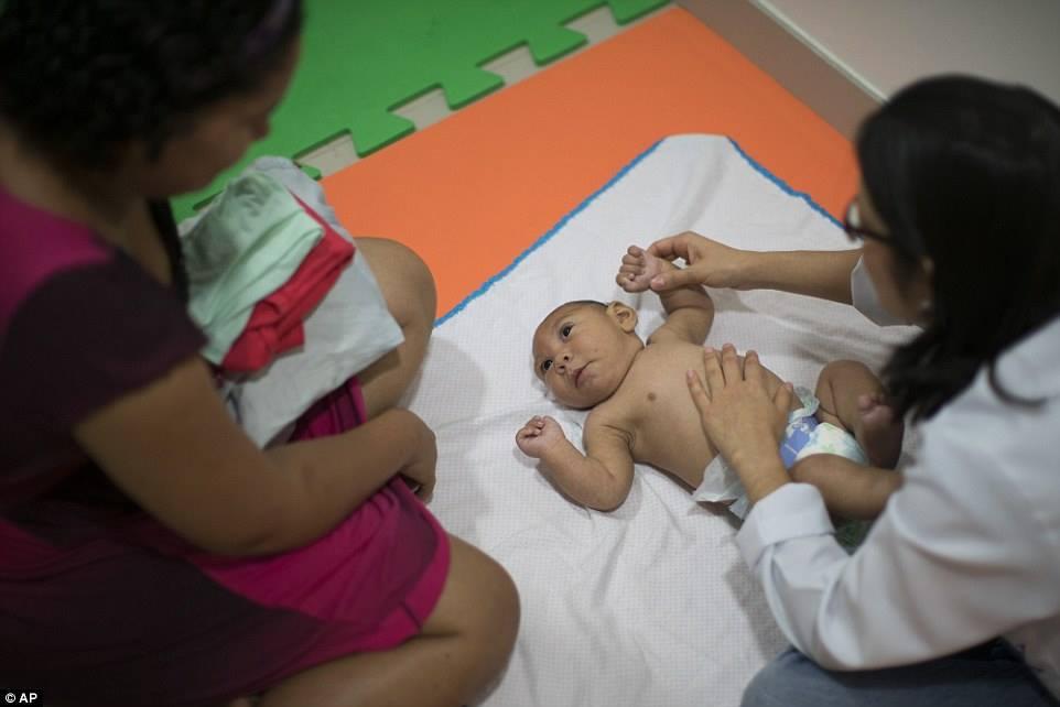 Jaqueline Vieira, trái, đang nhìn đứa con trai ba tuổi Daniel của chị. Bé bị mắc chứng đầu teo và đang được khám sức khỏe tại Altino Ventura foundation ở Recife.