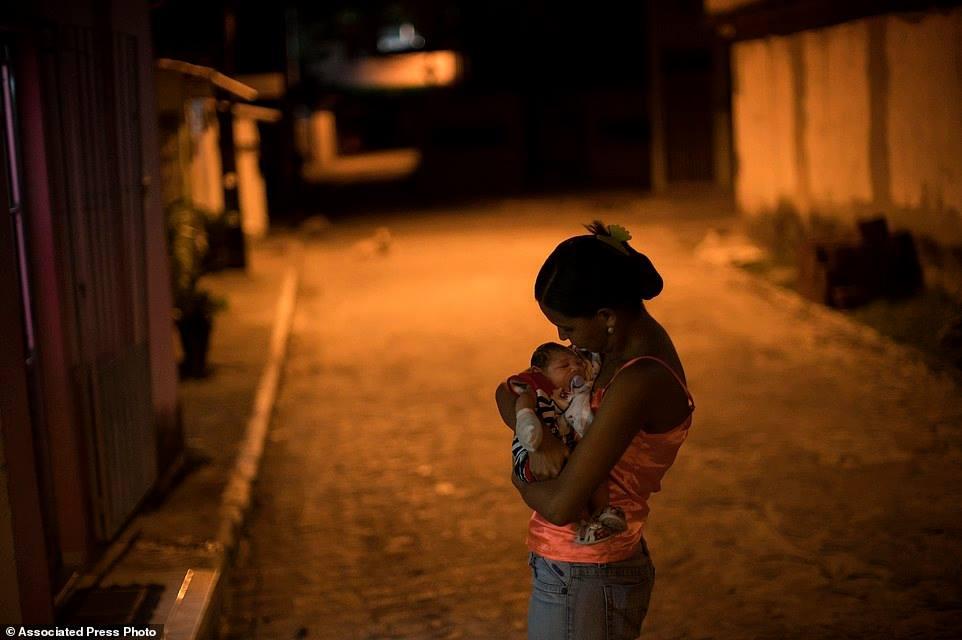 Chị Santos đang ẵm Juan Pedro – bé sinh ra mắc chứng đầu teo hồi tháng 12, bên ngoài căn nhà của chị ở Recife, chưa bao giờ được chẩn đoán nhiễm Zika, nhưng chị nguyền rủa con virus đã lây nhiễm cho con trai chị và những thiệt hại khủng khiếp nó gây ra cho cuộc sống của chị.