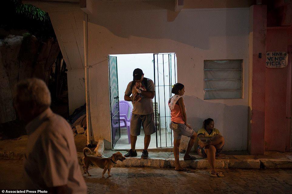 Chị Santos, giữa phải, đứng bên ngoàingôi nhà trong khi người chồng cũ ẵm Juan Pedro. Gần như từ lúc sinh, Pedro khóc suốt, cũng y như nhiều em bé đầu teo khác. Chồng chị không chịu nổi khi bé khóc hoài, làm anh không xem tivi được, nên một vài tuần sau khi Pedro về đến nhà, anh ta bỏ đi khỏi. Anh đi mang theo cái tivi màn hình phẳng, vật quý giá nhất của căn nhà nhỏ.
