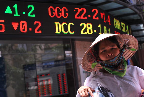 A street vendor walks past a local securities trading company in downtown Hanoi on May 21, 2010.  The biggest drop in more than a year on Wall Street triggered fresh turmoil in Asian markets on May 21, amid heightened anxiety over the eurozone debt crisis and doubts over the strength of the US economy. Vietnam's stocks plunged 4.11 percent keeping its falling trend for weeks. AFP PHOTO/HOANG DINH Nam (Photo credit should read HOANG DINH NAM/AFP/Getty Images)