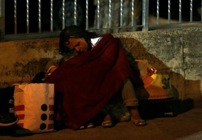 A woman sleeps covered with a blanket as she spends the night in the open following an earthquake in Amatrice, central Italy, August 24, 2016. REUTERS/Stefano Rellandini