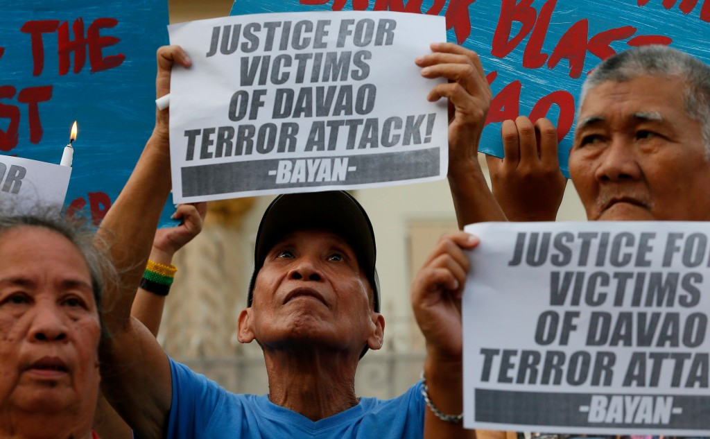 """Protesters display placards during a prayer vigil in Manila, Philippines, for the victims of Friday night's explosion in Davao city southern Philippines, Saturday, Sept. 3, 2016. Philippine President Rodrigo Duterte declared a nationwide """"state of lawlessness"""" Saturday after suspected Abu Sayyaf extremists detonated a bomb at the night market in Davao city, his hometown, killing a number of people. (AP Photo/Bullit Marquez)"""