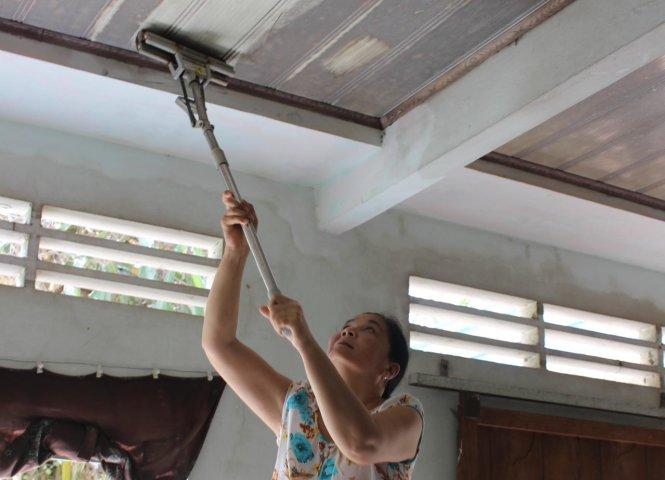 Bà Trần Thị Dung (thị trấn Mái Dầm, huyện Châu Thành, Hậu Giang) chứng minh trần nhà mình bám đầy bụi mà bà cho rằng từ hoạt động của nhà máy giấy Lee&Man gần đó gây ra (ảnh T.Trình)