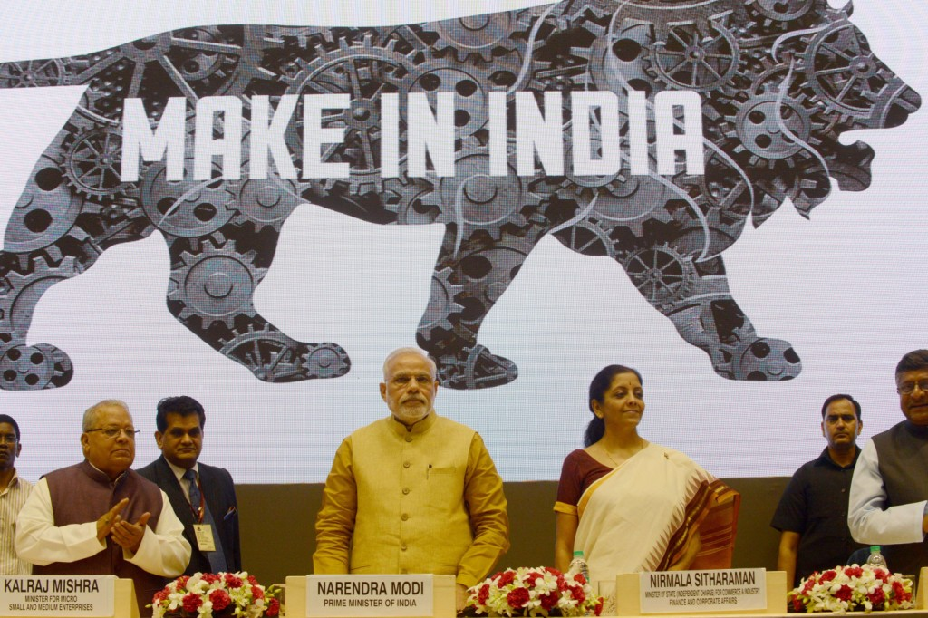 """Indian Prime Miniser Narendra Modi (C) launches the """"Make In India"""" project as Minister for Commerce and Industry Nirmala Sitaraman looks on in New Delhi on September 25, 2014. Prime Minister Narendra Modi pledged September 25 to slash red tape and harness the benefits of a huge young population as he launched a campaign to attract global business to manufacture in India. India's business-friendly new leader wants to revive his country's flagging economic fortunes by kickstarting a manufacturing sector long eclipsed by that of neighbouring China.  AFP PHOTO/RAVEENDRAN        (Photo credit should read RAVEENDRAN/AFP/Getty Images)"""